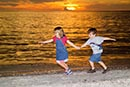 two children running on beach at sunset
