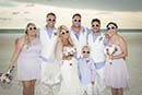 Wedding party on beach all wearing sunglasses