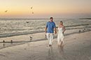 bride and groom walking on beach at sunset